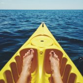Man tanned legs in yellow kayak
