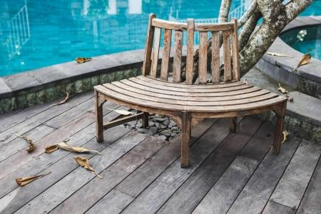 Wooden bench near swimming pool