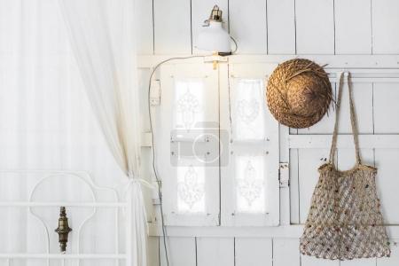 Photo pour Intérieur de la maison en bois moderne de lumière à l'intérieur, fenêtre vintage avec volets et rideaux décoratifs. Chapeau de paille et sac en osier fait main. Style rustique et villageois - image libre de droit