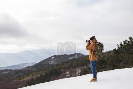 Tourist taking photo of mountains