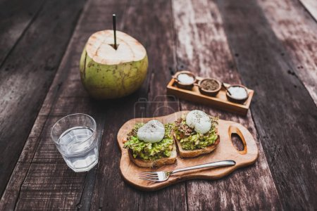 Tasty organic healthy breakfast - poached eggs on toast with avocado, water with lime, young coconut. Dark wooden background