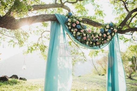 Sonnenuntergang Hochzeitszeremonie Bogen mit Blumendekoration und blauen Klo