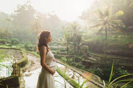 Photo pour Jeune femme enceinte en robe blanche avec vue sur les terrasses de riz de Bali au soleil du matin. Harmonie avec la nature. Concept de grossesse . - image libre de droit