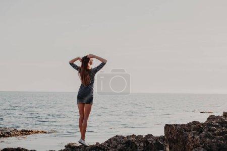 Photo pour Jeune fille sur la plage rocheuse ressemble en mer 1 - image libre de droit