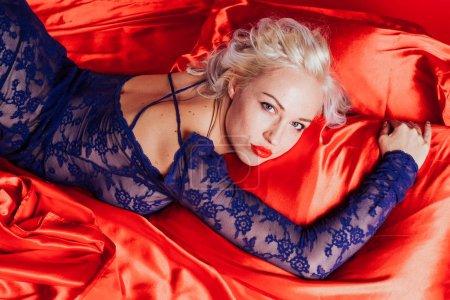 Photo pour Jeune fille blonde sexy en lingerie violette se trouve sur le lit rouge - image libre de droit