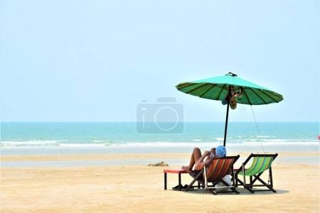 Photo for Man sit on beach chair with umbrella - Royalty Free Image