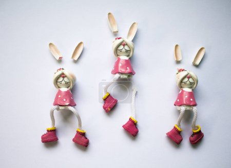 Photo for Broken toys on white background. Flat image of broken rabbit with closed eyes. Ceramic figurine broken. Concept for broken child, childhood trauma, pedophilia, frightened kid. Bunny girl in pink dress - Royalty Free Image