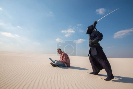 Man with laptop above him is a samurai with a sword, as an deadl