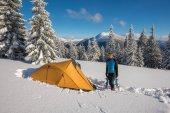 Traveler stands in a deep snow near a tent