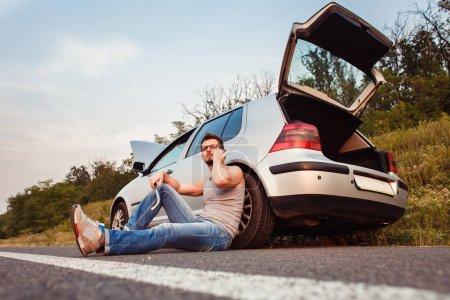 Photo pour Un jeune homme est assis sur l'asphalte, près de sa voiture cassée et appelle le support technique. Dommages sur la route - image libre de droit