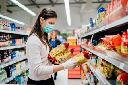 Photo for Buyer wearing a protective mask.Shopping during the pandemic quarantine.Nonperishable smart purchased household pantry groceries preparation.Woman buying few pasta packages.Budget pastas and noodles. - Royalty Free Image