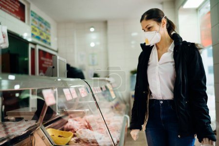 Photo for Woman with protective mask shopping for supplies.Budget shopping.Buying fresh meat at a butchery.Beef,pork,chicken infection.Preparation for a pandemic quarantine due to covid-19.Meat shortage - Royalty Free Image