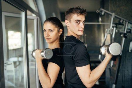 Photo pour Jeunes entraîneurs de conditionnement physique athlétique.Entraînement en couple actif ensemble.Entraînement d'haltère.Adapter la femme et l'homme côte à côte, entraînement en partenaire.Entraîneurs de conditionnement physique exerçant dans la gymnase. - image libre de droit