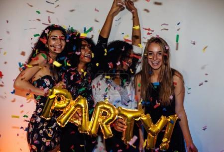Photo pour Groupe de jeunes femmes célébrant avec des confettis, debout à l'intérieur - image libre de droit