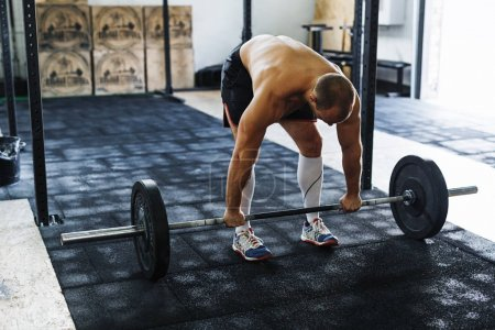 Young athlete preparing for deadlifting in gym