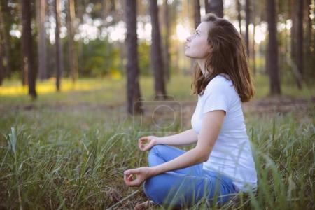Photo pour Femme pratique l'yoga et médite dans la position du lotus sur la nature. Fille de méditer à la forêt. Femme, méditer dans la position du lotus closeup - image libre de droit