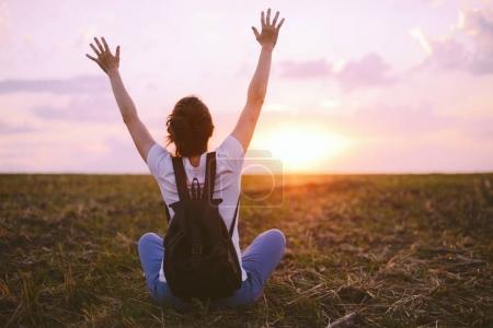 Photo pour Jeune femme se détendre dans le ciel d'été coucher de soleil en plein air. Style de liberté du peuple. - image libre de droit