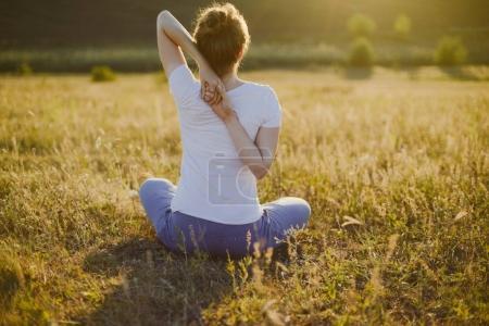 Photo pour Jeune femme est assis dans la pose de yoga namaste avec la ville sur le fond. Concept de liberté. Calme et détente, bonheur des femmes - image libre de droit