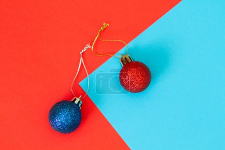 Photo for Two New Year's balls on the color blue and red paper. Christmas toys with sparkles. - Royalty Free Image