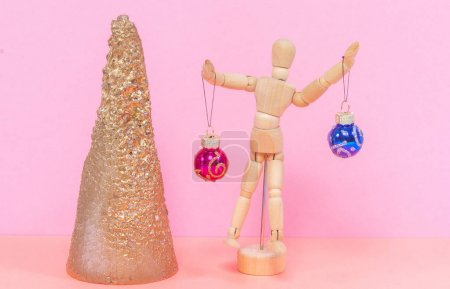 Photo for Wooden man holds two New Year's balls. Nearby is a golden cone in the form of a Christmas tree. Christmas and New Year concept. - Royalty Free Image