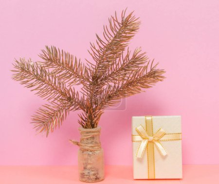 Photo for Christmas tree branch in a glass vase. Box with a gift on a pink background. Composition in pastel colors. New Year, Christmas and birthday concept. Empty space for text. - Royalty Free Image