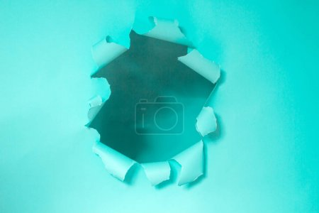 Photo for Torn paper in the form of a circle. A hole in cardboard. Blue background. Place for text. - Royalty Free Image