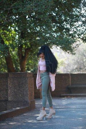 Stylish female walking in park