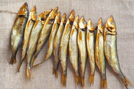 Smoked herring fish. Delicious smoked fish on the burlap.
