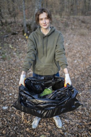 Photo pour Beautiful student shows garbage collected in nature. Social advertising of active lifestyle and environmental assistance. - image libre de droit