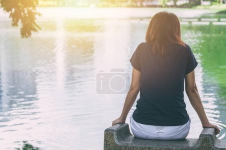 Photo pour Adolescent assis seul se sentant seul et pensant manquer quelqu'un regardant le lac d'eau - image libre de droit