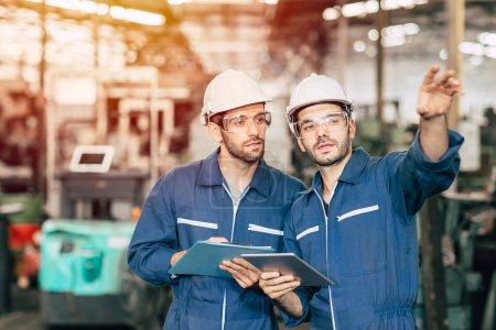 Photo pour Deux ingénieurs travaillent ensemble avec un uniforme de sécurité et un casque blanc dans une tablette à poignée d'usine. - image libre de droit