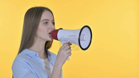 Photo pour Belle femme faisant une annonce sur un haut-parleur, fond jaune - image libre de droit