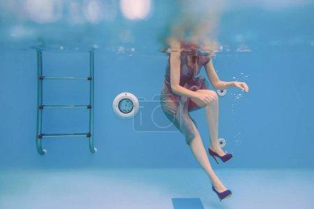 Photo pour Portrait d'art surréaliste de jeune femme en robe grise, écharpe perlée, petit sac, talons hauts violets sous l'eau dans la piscine - image libre de droit