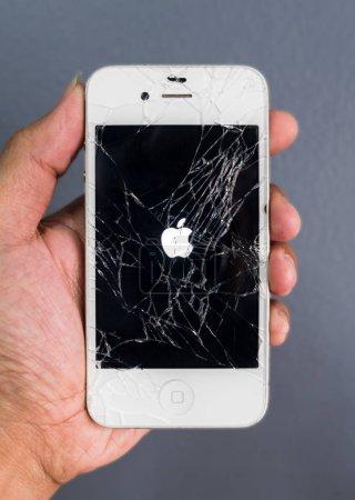 Human hand holding broken Apple iPhone smartphone