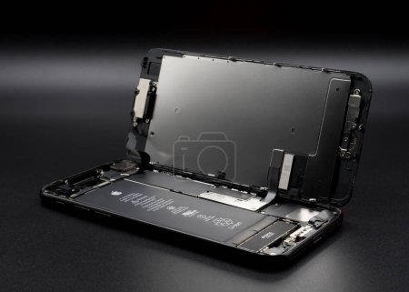Photo for Chiangrai, Thailand: May 19, 2017 - Apple iPhone 7 jet black color disassembled for repair and showing components inside on black background. Selective focu - Royalty Free Image