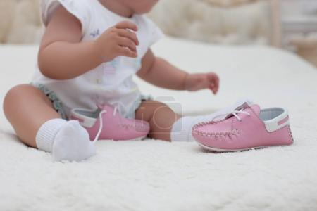 Infant girl wearing pink shoes