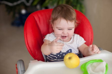 Infant girl sitting in highchair with apple