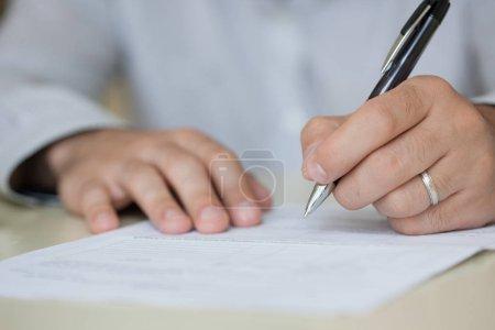 Mann schreibt etwas auf Blatt Papier