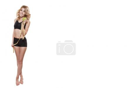 Girl standing with apple and tape measure