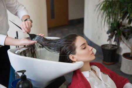 Hairdresser dyeing hair for customer