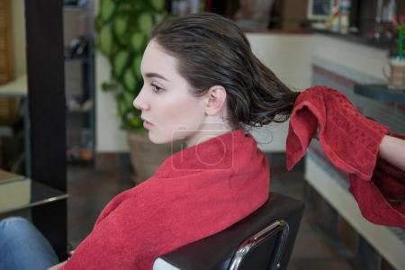 Hairdresser drying hair with red towel