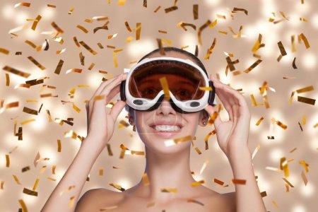 Photo pour Jeune jolie femme masquée pour le ski célébrant et s'amusant à la fête du Nouvel An . - image libre de droit