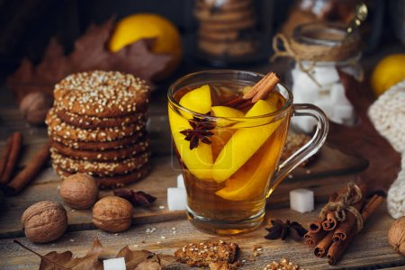 Autumn hot tea with lemon in glass cup.