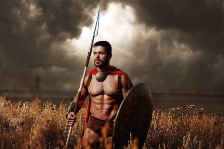 Photo for Pure masculinity. Sepia toned shot of a young athletic Greek warrior standing in the field armed with a spear and a shield posing under gloomy skies looking away thoughtfully trustworthy confidence - Royalty Free Image