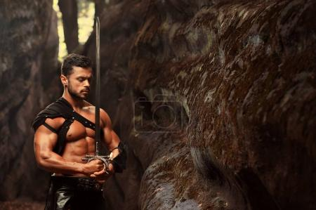Photo for Deep in his thoughts. Horizontal portrait of well-built muscular young warrior standing with a sword with his eyes closed near the rock at the woods - Royalty Free Image