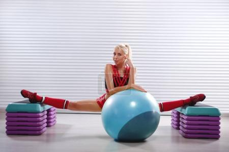 Beautiful young flexible fitness woman doing splits during her w