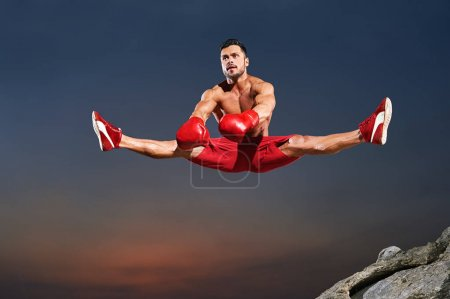 Male athlete doing splits in the air while jumping