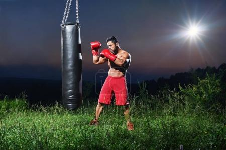 Young handsome male boxer practicing on a punching bag outdoors