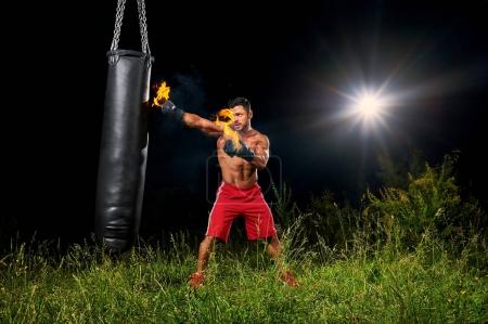 Professional boxer punching sandbag outdoors with his boxing glo