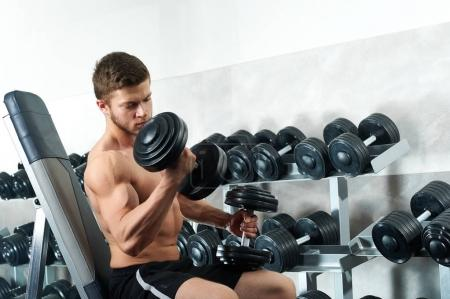 Handsome young athlete working out at the gym